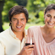 Two friends looking ahead while holding glasses of wine — Stock Photo
