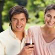 Stock Photo: Two friends looking ahead while holding glasses of wine