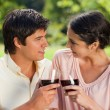 Two friends looking at each other while touching glasses of wine — Stock Photo