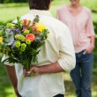 Man about to surprise his friend with a bouquet of flowers - Foto Stock
