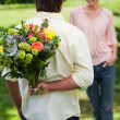 Man about to surprise his friend with a bouquet of flowers - Stock Photo