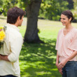 Woman smiling as her friend approaches her with flowers — Stock Photo #10329606