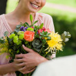 Stock Photo: Woman holding flowers which she has been given