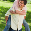 Man looking to his side while carrying his friend on his back — Stock Photo