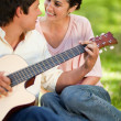 Man playing a guitar while looking at his friend — Stock Photo