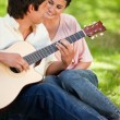 Woman smiling while watching her friend play the guitar — Stock Photo