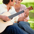 Woman smiling while her friend plays the guitar — Stock Photo