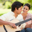 Man playing the guitar while his friend watches him — Stock Photo