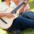 Man playing the guitar while his friend is listening to him - Stock Photo
