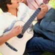 Man playing the guitar while his friend leans on his shoulder — Stock Photo