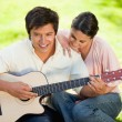Woman leaning while leaning on her friends shoulder as he plays — Stock Photo #10329711