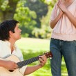 Woman standing in admiration of her friend who is playing the gu - Stock Photo