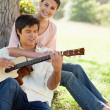 Woman holding her friend as her plays the guitar — Stock Photo #10329719