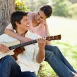 Woman looking at her friend while holding him as her plays the g — Stock Photo #10329721