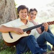 Man playing the guitar while ahead with his friend — Stock Photo #10329728