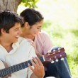 Woman laughing with her friend who is playing the guitar — Stock Photo