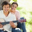 Woman smiling with her friend who is holding a guitar — Stock Photo