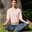 Woman sitting in a yoga position near a tree — Stock Photo