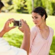 Man takes a photo of his friend while she poses — Stock Photo #10329807
