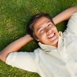 Man smiling as he lies with both hands behind his neck — Stock Photo #10329869