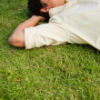 Man lying in grass with his eyes closed and both hands behind hi — Stock Photo #10329873