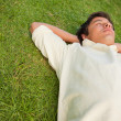 Man lying in grass with his eyes closed and his head resting on - Foto Stock