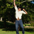 Man jumping with his arms raised as he rejoices - Stock Photo