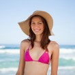 Smiling teenage girl wearing a hat while standing on the beach — Stock Photo