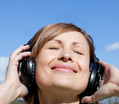 Happy woman is listening music outdoor — Stock Photo