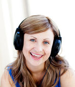 Cute woman is listening the music with headphones — Stock Photo