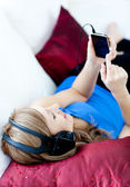 Delighted woman is listening the music with headphones — 图库照片