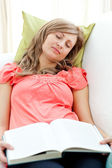 Tired woman reading a book lying on a sofa in the living-room — Stock Photo