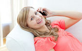 Happy woman talking on phone lying on a sofa — Stock Photo