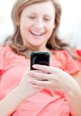Laughing woman sending a text lying on a sofa — Stock Photo