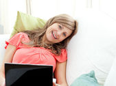 Jolly woman using a laptop sitting on a sofa — Stock Photo