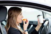 Charming businesswoman eating and holding a drinking cup while d — Stock Photo