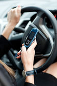 Close-up of a businesswoman sending a text while driving — Stockfoto