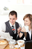 Smiling couple of business reading a newspaper while havi — Fotografia Stock