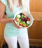 Beautiful woman showing a salad — Stock Photo