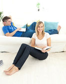 在客厅里可爱的夫妇阅读本书 — 图库照片