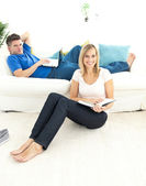 United couple reading book in the living-room — Stock Photo