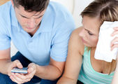 Adorable couple using a remote in the living-room — Stock Photo