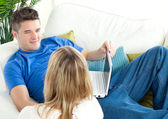 Young couple using a laptop together on a sofa — Stock Photo