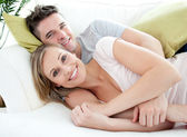 Smiling lovers having fun together on a sofa — Stock Photo