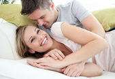 Joyful lovers having fun together on a sofa — Stock Photo