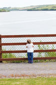 Little child standing in front of a fence — Stock Photo