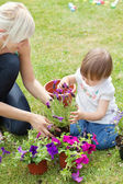 Glowing mother and her daughter with flowers — Stock Photo