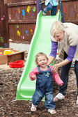 Little girl standing before a green chute — Stock Photo
