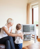 Family looking to the television — Stock Photo