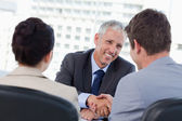 Entrepreneurs shaking the hand of their banker — Stock Photo